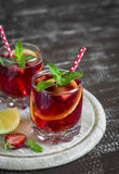 Lemonade with strawberries, lemon and mint in glass beakers Stock Photo