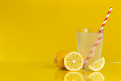 Lemonade. Studio shot of a glass of lemonade with a striped red and white drinking straw and a whole, cross section and a slice of lemon fruit placed next to it Stock Photo