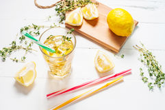 Lemonade with thyme served in glass with a straw on a white wooden table. Royalty Free Stock Photos