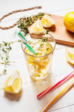Lemonade with thyme served in glass with a straw on a white wooden table. Royalty Free Stock Images