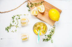 Lemonade with thyme served in glass with a straw on a white wooden table. Royalty Free Stock Image