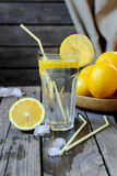 Lemonade in a transparent glass and lemons on a  wooden table Stock Photos