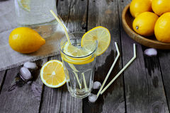 Lemonade in a transparent glass and lemons on a  wooden table Royalty Free Stock Photography