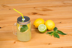 Lemonade with two lemons, a lime and mint, wood background Royalty Free Stock Image
