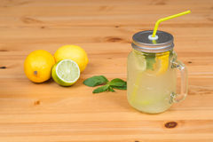 Lemonade with two lemons, a lime and mint, wood background Stock Photo