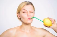 Lemonade vitamin beverage. Healthy lifestyle and organic nutrition concept. Girl drink fresh juice whole lemon fruit royalty free stock image