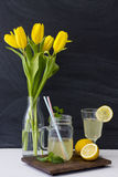 Lemonade and yellow tulips in glass bottles Stock Images