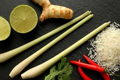 Lemongrass, red chili peppers, limes and jasmine rice, galangal and few coriander leaves on slate board, top view. Lemongrass, three red chili peppers, limes Royalty Free Stock Image