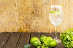 Lemoniada w szkle i zieleni cytrynie na drewnianym tle Napój dla zdrowie Obraz Royalty Free