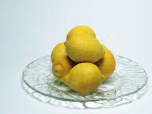 Lemons. On a plate on a plain background Stock Photos