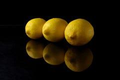Lemons. Three lemons on black background stock photos