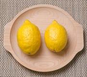 Lemons. Two fresh lemons in a wood bowl Royalty Free Stock Photo