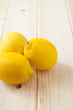 Lemons. Three yellow lemons on clear wood table Royalty Free Stock Image