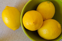 Lemons. In green bowl on burlap royalty free stock images