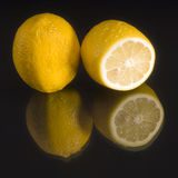 Lemons. Pair of lemons on black mirror  backround Royalty Free Stock Photography