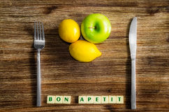 Lemons and apple on wooden vintage table with silverware. And Bon apetit sign Royalty Free Stock Image