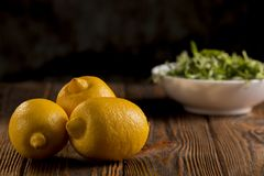 Lemons and arugula on a wooden table. Close up Stock Image