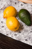 Lemons and avocado on table. A close up of a pair of lemons and avocado on a table Stock Photos