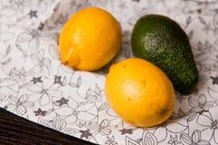 Lemons and avocado on table. A close up of a pair of lemons and avocado on a table. Whole series with sebczseries925 keyword Stock Image