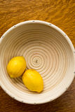 Lemons in a basket. Two ripe yellow lemon citrus fruit in a white basket Royalty Free Stock Image