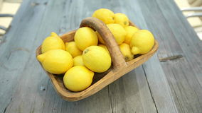 Lemons in a basket on a wooden table. Dolly shot stock video footage