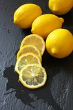 Lemons on black. Sliced lemons on wet black slate background Royalty Free Stock Photos