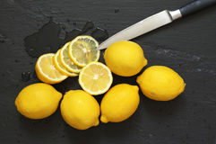 Lemons on black. Whole and cut lemons with knife on wet black slate background. Top view point Stock Photo