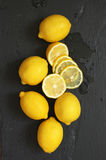Lemons on black. Whole and cut lemons on wet black slate background. Top view point Royalty Free Stock Photos