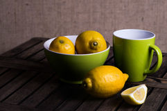 Lemons in a bowl with a mug of tea. Fresh tangy yellow lemons in a green ceramic bowl with a matching mug of tea and cut quarter fruit in the foreground stock photos