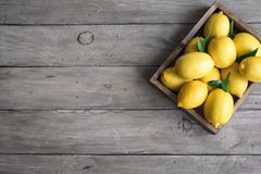 Lemons in box. Lemons with green leaves in box on wooden background, top view, copy space. Organic fresh citrus fruits lemons royalty free stock photos