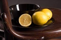 Lemons on chair. Cup with saucer and lemons on chair stock image