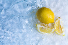 Lemons in cool refreshing water. A whole and sliced fresh yellow lemon floating in cool refreshing water with copyspace stock photos