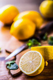Lemons cut into the old kitchen board with mint leaves Royalty Free Stock Photos