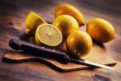 Lemons cut into the old kitchen board with mint leaves Stock Image