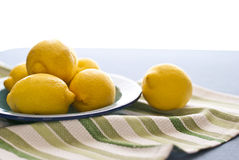 Lemons In a Dish. Six lemons in a pretty dish placed on a new green-striped dish towel Royalty Free Stock Photography