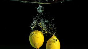 Lemons dropping in water