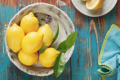 Lemons. Fresh lemons with leaves in rustic ceramic bowl over wooden background. Macro, selective focus, vintage style stock images