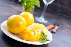 Lemons. Fresh lemons with mint leaves on a table Royalty Free Stock Image
