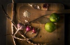 Lemons, garlics, sesame, beans on wood cropping block. Stock Images