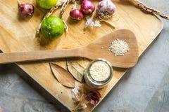Lemons, garlics, sesame, beans on wood cropping block. Royalty Free Stock Image