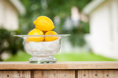 Lemons in a glass bowl at a lemonade stand. A glass bowl of lemons sitting on the counter of an outdoor lemonade stand Royalty Free Stock Image