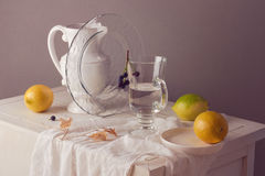 Lemons and glass of water on table. Rustic still life composition Stock Image