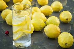 Lemons. With a glass of water on a glass table with tree reflexion royalty free stock photo
