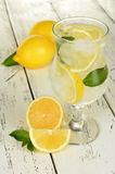 Lemons in a glass with water on white wooden background Stock Images