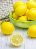 Lemons in a green bowl. On wooden background Stock Photo