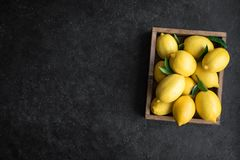 Lemons. With green leaves in box on black stone background, top view, copy space. Organic fresh citrus fruits stock image