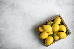 Lemons. With green leaves in box on white stone background, top view, copy space. Organic fresh citrus fruits stock photo