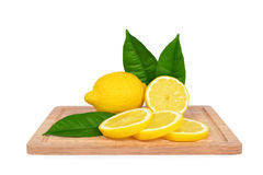 Lemons with green leaves on wooden cutting board Royalty Free Stock Photos