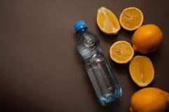 Lemons on grey background and juice bottle Stock Photos