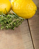 Lemons and herbs on a wooden table Royalty Free Stock Photography